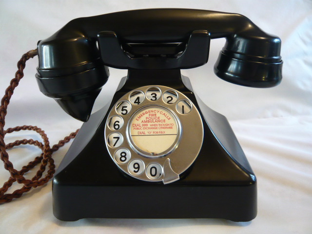 Old Bakelite dial up phone with emergency number 999 on the label